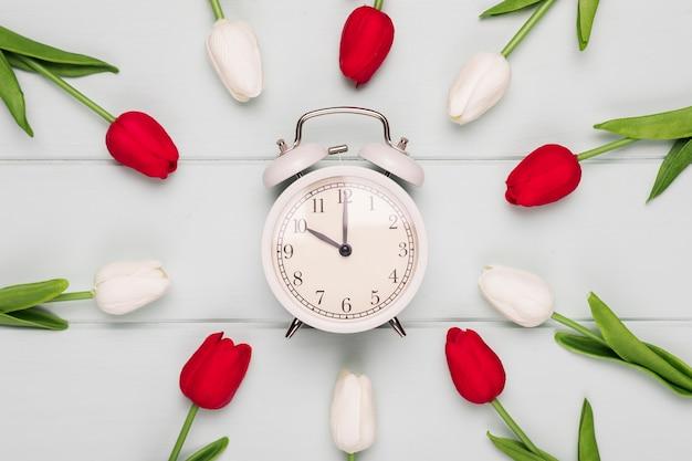 Quadro de tulipas coloridas com relógio na mesa