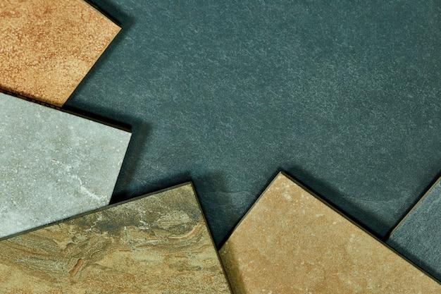 Quadro de várias amostras decorativas diferentes das telhas no fundo de pedra.