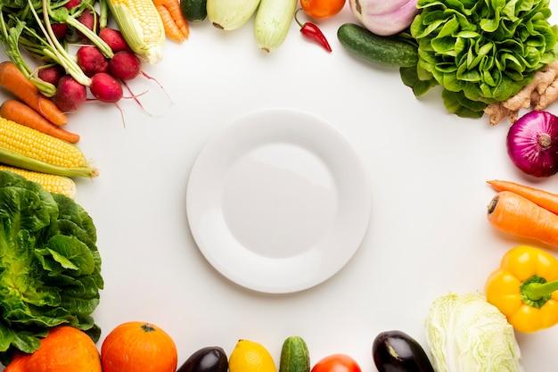 Quadro de vegetais de vista superior com prato vazio