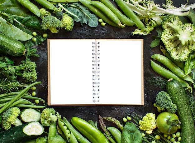 Quadro de vegetais verdes com caderno em uma mesa escura close-up