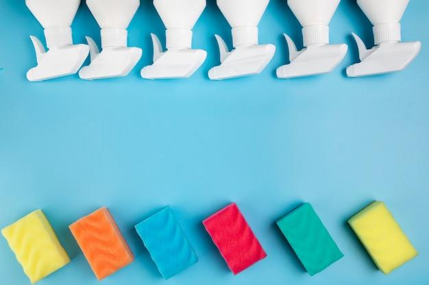 Quadro de vista superior com frascos de spray e esponjas coloridas