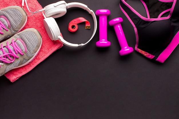 Quadro de vista superior com itens-de-rosa e fones de ouvido brancos
