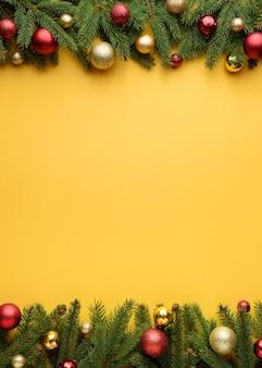Quadro decorativo de galhos de pinheiro e bolas de natal. fundo amarelo para o projeto de natal. copie o espaço para promoções e texto de parabéns