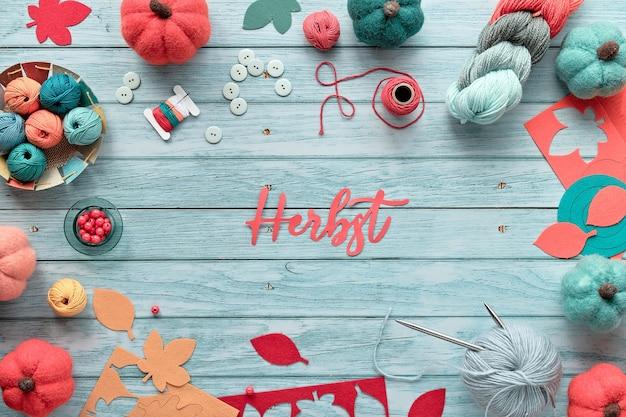 Quadro decorativo feito de feixes de lã, bolas de lã, abóboras de feltro decorativas e coloridas folhas de outono. texto em papel herbst significa outono na língua alemã. plano sazonal de outono em madeira azul claro.