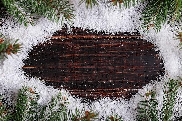 Quadro do fundo do natal, árvores de natal verdes em uma tabela de madeira, tracejada pela neve branca, espaço da cópia, vista superior.