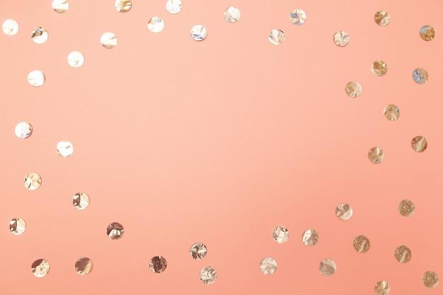 Quadro dos confetes de prata brilhantes no fundo de papel cor-de-rosa millennial pastel.