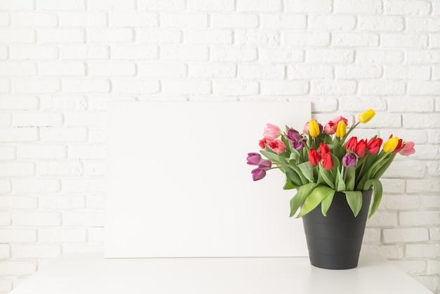 Quadro e balde de tulipas no fundo da parede de tijolo branco