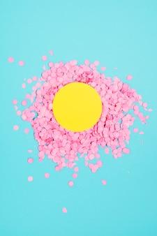Quadro em branco amarelo sobre o confete rosa pequeno circular festivo contra o fundo azul
