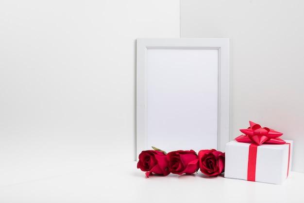 Quadro em branco com caixa de presente e rosas