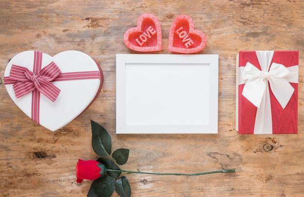 Quadro em branco com caixas de presente na mesa de madeira