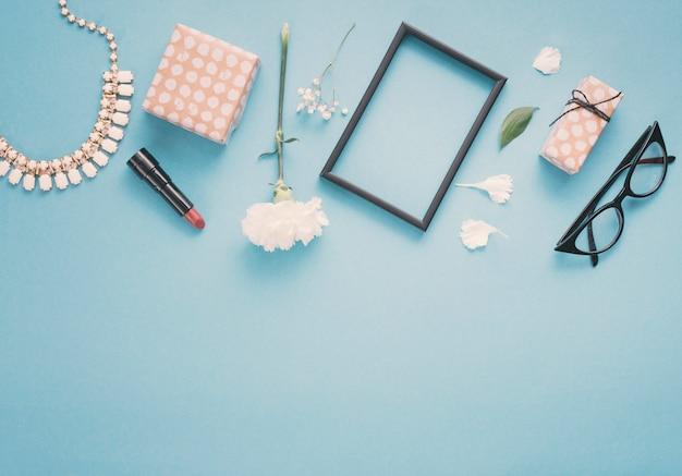 Quadro em branco com flores, caixas de presente e batom na mesa