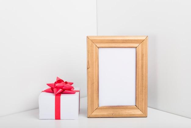 Quadro em branco com pequena caixa de presente na mesa