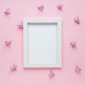 Quadro em branco com pequenas flores roxas na mesa