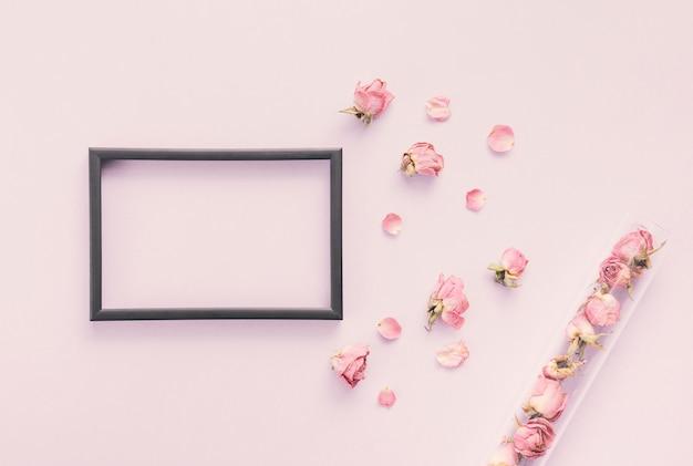 Quadro em branco com pétalas de rosa na mesa