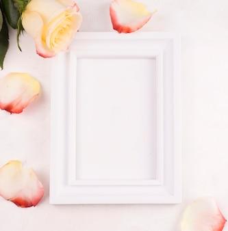 Quadro em branco com pétalas de rosas