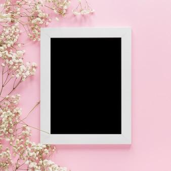 Quadro em branco com ramos de flores na mesa