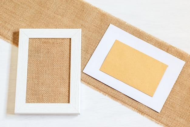 Quadro em branco de desperdício zero para design de cartão. porta-retrato de madeira branca com tecido de smoking de estopa, envilope artesanal com espaço de cópia. mock up feito à mão, conceitos de diy.