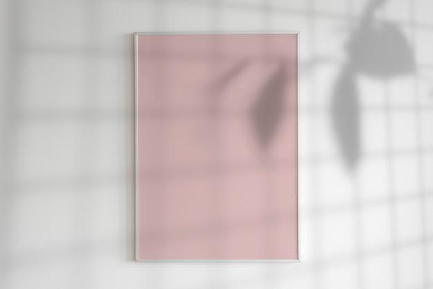 Quadro em branco em uma parede com sombra de planta