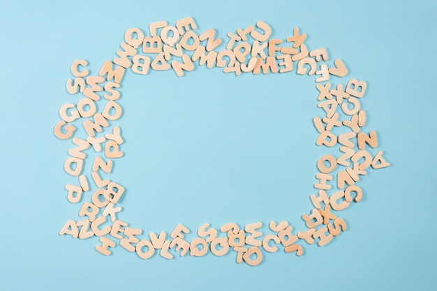 Quadro em branco feito com alfabetos de madeira no fundo azul