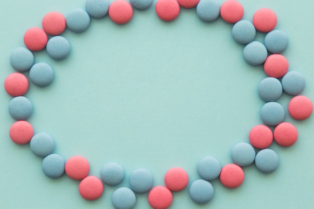 Quadro em branco, feito com doces circulares-de-rosa e azuis em pano de fundo colorido