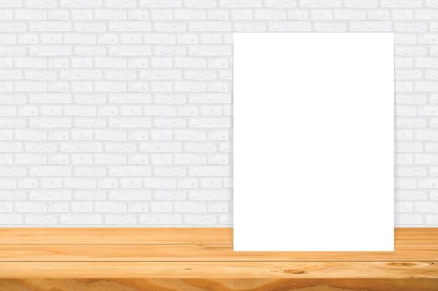 Quadro em branco na mesa de madeira na parede de azulejo branco