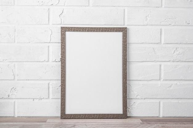 Quadro em branco na prateleira na parede branca