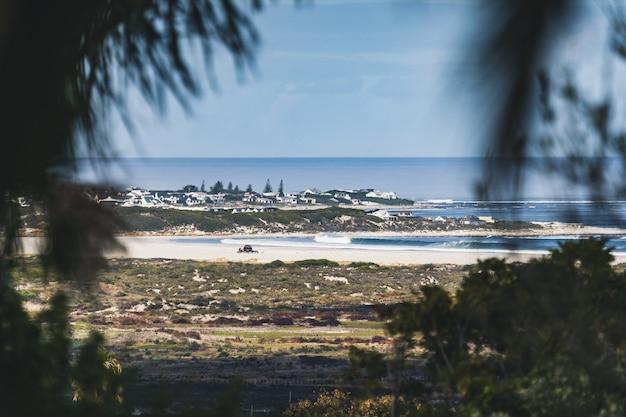 Quadro em um quadro quente de uma costa de vila sob um céu azul claro