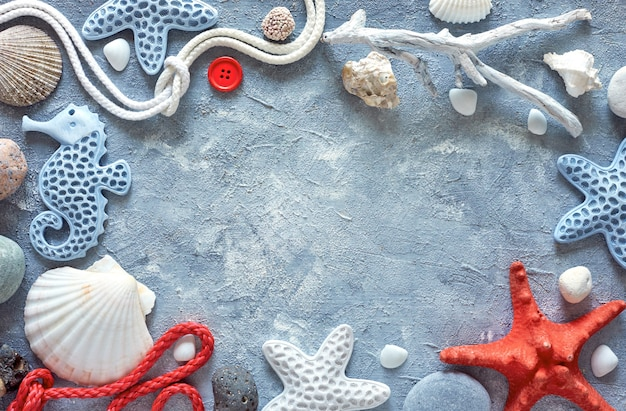 Quadro feito de conchas do mar, pedras, corda e peixe estrela no plano de fundo texturizado azul, cópia-espaço