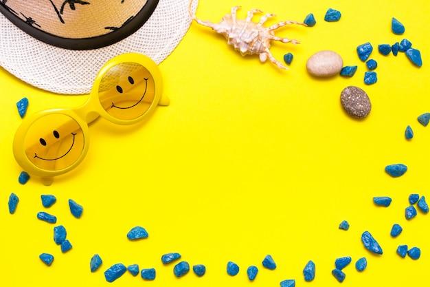 Quadro feito dos óculos de sol com um sorriso, um chapéu, umas pedras decorativas e um shell em um fundo amarelo. vista do topo