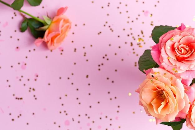 Quadro festivo de canto de flores rosas frescas e estrelas de confetes brilhantes decorativos de carnaval na luz rosa.