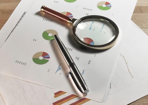 Quadro financeiro em papéis com lupa e caneta documentos de contabilidade de negócios com finanças m ...