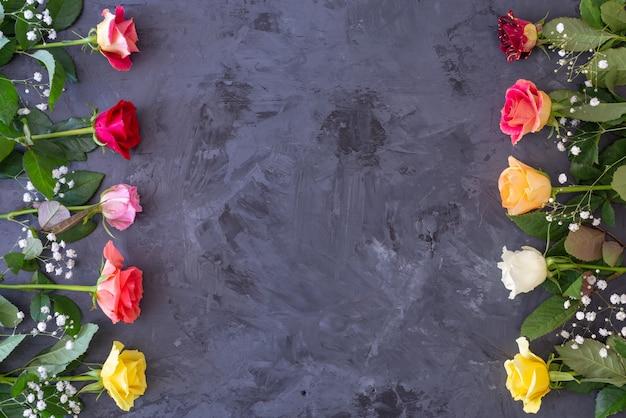 Quadro floral com rosas coloridas sobre fundo cinza / preto, flat lay, vista superior