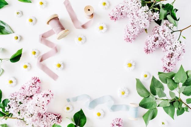 Quadro floral de flores lilás, ramos frescos de camomila e carretel com fita azul e bege em fundo branco vista superior plana