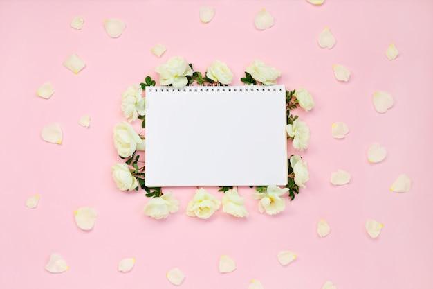 Quadro floral de rosas brancas e pétalas ao redor do caderno