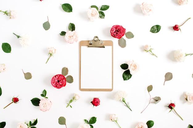 Quadro floral plano leigo com prancheta, padrão de botões de flores rosa vermelha e bege em fundo branco. vista do topo
