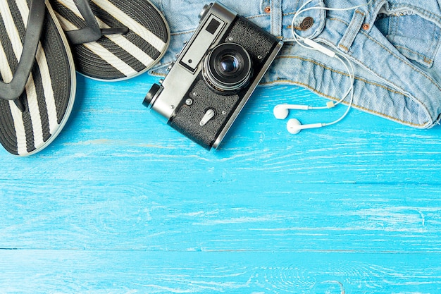 Quadro fones de ouvido fêmeas elegantes da câmera das calças de brim dos deslizadores no fundo de madeira azul, copyspace, férias de verão.