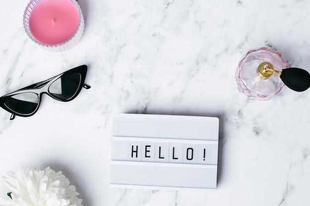 Quadro hello em uma mesa de mármore com uma flor e uma vista superior de óculos