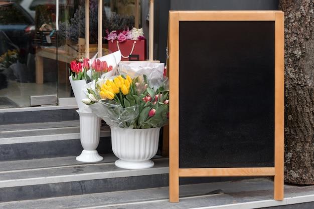 Quadro indicador na rua, carrinho de placa de menu vazio, placa de sinalização de lousa de calçada de restaurante, quadro-negro de quadro independente perto da loja de flores, copyspace para texto, foco seletivo.