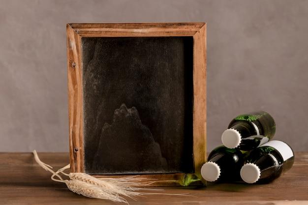 Quadro negro ao lado de três garrafas de cerveja na mesa de madeira