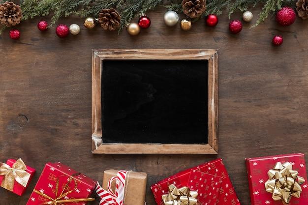 Quadro-negro com caixas de presente brilhante na mesa