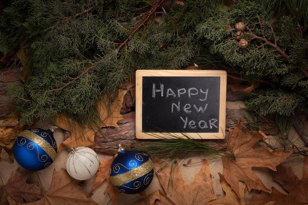 Quadro-negro com felicitações de ano novo em fundo de madeira com folhas amarelas e bolas