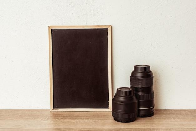 Quadro-negro com lentes de câmera em uma prateleira de madeira. lugar para inscrição, um conceito de publicidade para uma escola de fotografia