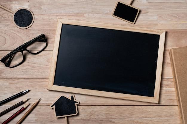 Quadro-negro com material escolar, caderno e quadro-negro em uma mesa de madeira.