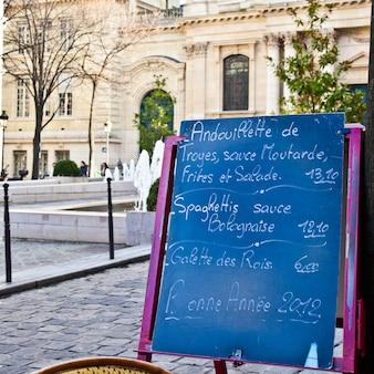 Quadro negro com menu de restaurante em praça tradicional típica de paris