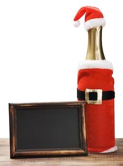 Quadro-negro com moldura de madeira e uma garrafa de champanhe em uma roupa de papai noel