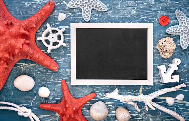Quadro-negro com moldura feita de conchas do mar, pedras, corda e peixe estrela no azul texturizado, cópia-espaço