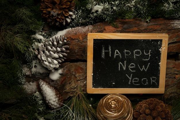 Quadro-negro com parabéns de feliz ano novo em fundo de madeira com galhos