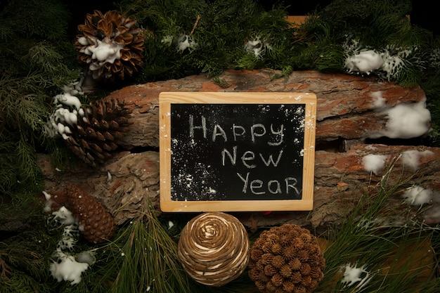 Quadro-negro com parabéns de feliz ano novo em fundo de madeira com ramos de pinheiro
