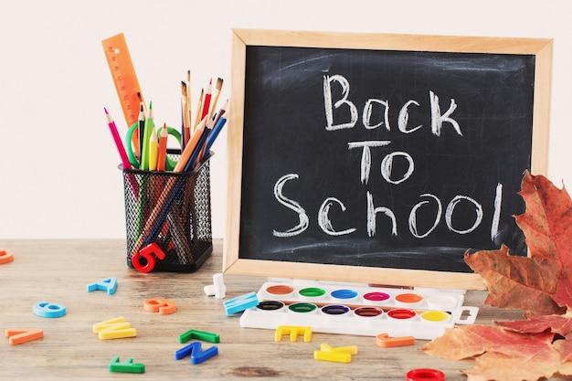 Quadro-negro com texto e material escolar na mesa de madeira, de volta ao conceito de escola
