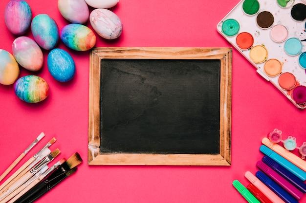 Quadro-negro de madeira cercado com ovos de páscoa; pincéis de pintura; canetas de ponta de feltro e caixa de pintura de cor de água no fundo rosa